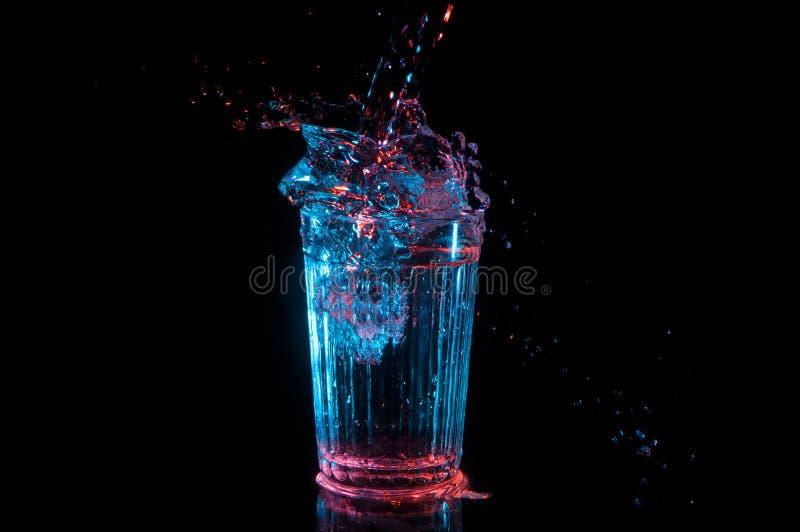 Grande spruzzata della bevanda da vetro d'annata alle luci rosse e blu isolate su un fondo nero fotografia stock libera da diritti