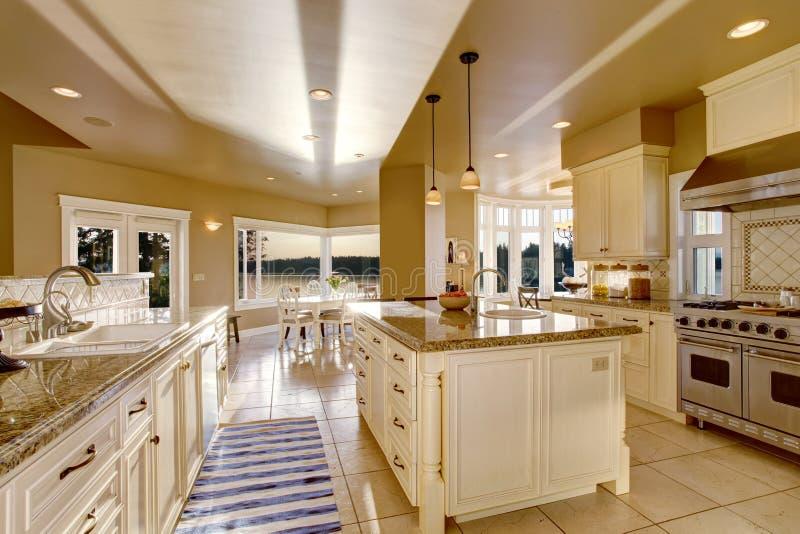 Grande stanza di lusso della cucina nei colori beige con i ripiani del granito e l'isola di cucina immagini stock libere da diritti