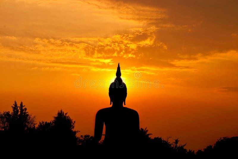 Grande statua del buddha della siluetta contro il tramonto immagini stock