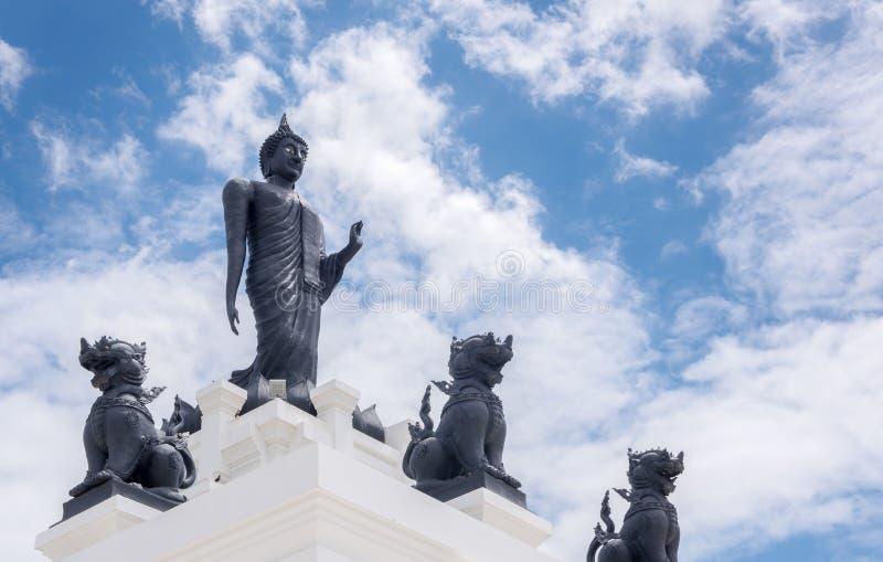 Grande statue noire de Bouddha avec le ciel nuageux et bleu blanc images stock