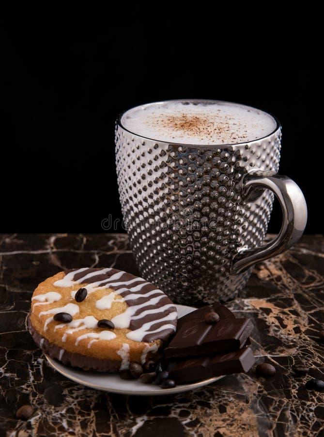 Grande tasse argentée pimpled de bisquits chocolat de café et de gâteaux et grains de café sur la surface et le noir de granit image stock