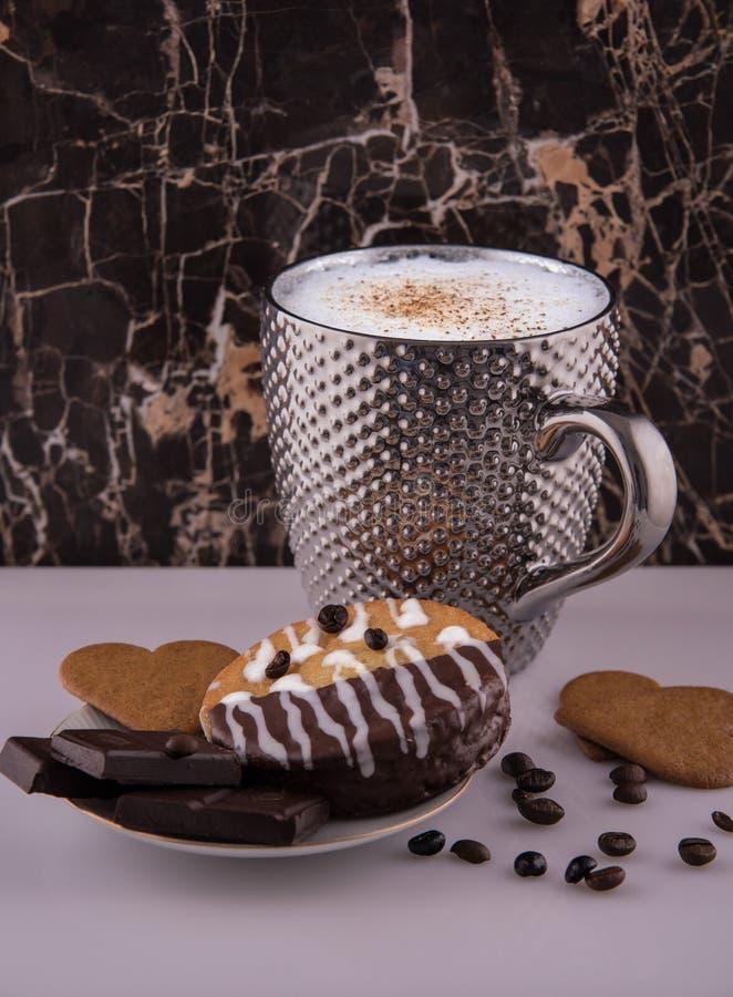 Grande tasse argentée pimpled de bisquits chocolat de café et de gâteaux et grains de café sur la surface réfléchie blanche images stock
