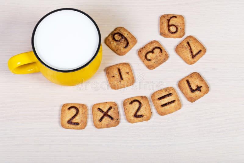Grande tazza gialla di latte e dei biscotti divertenti con i numeri su fondo di legno leggero Prima colazione sana per un bambino fotografia stock