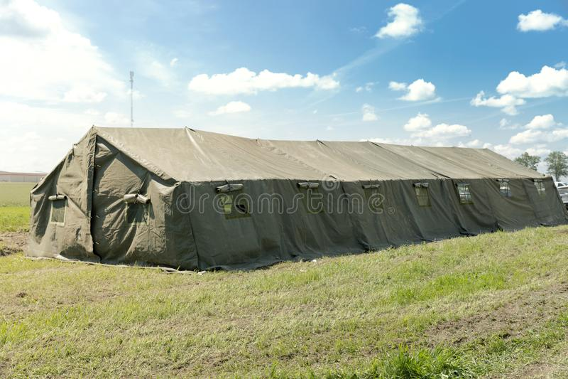 Grande tente militaire dans le ciel bleu lumineux d'agaist de champ photo stock