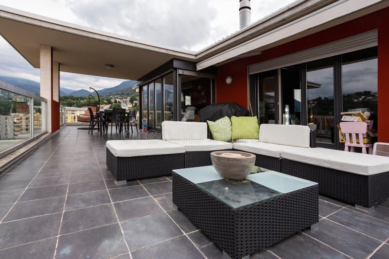 Grande terrazzo ammobiliato di mobilia all'aperto immagini stock