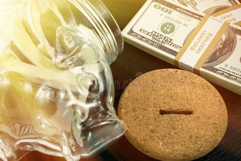 Grande tirelire de tirelire, pot en verre d'argent avec des briques de 100 dollars US, effet de rayon de soleil image libre de droits