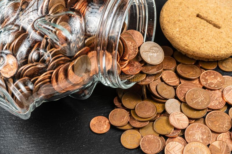 Grande tirelire de tirelire, pot en verre d'argent avec les pièces de monnaie britanniques photo stock