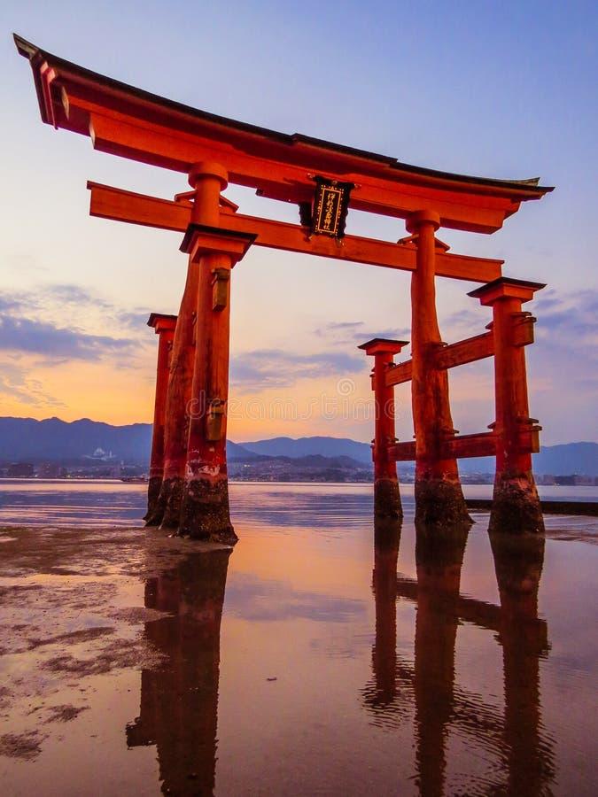 Grande Torii do santuário xintoísmo de Itsukushima no por do sol imagem de stock