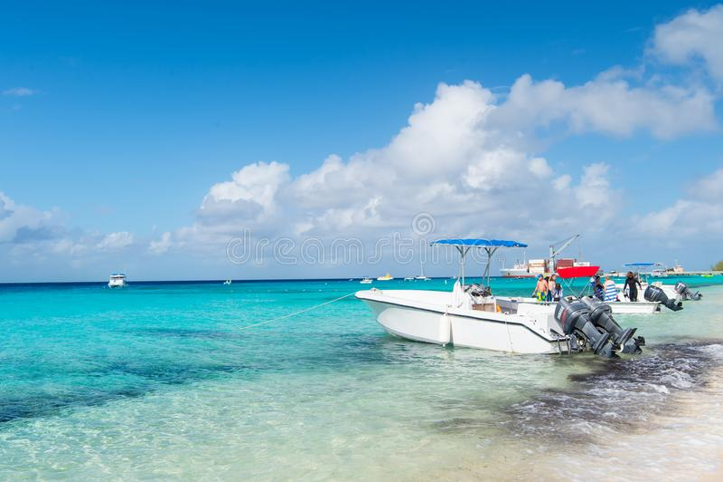 Grande Turco, Isole Turks e Caicos - 29 dicembre 2015: imbarcazioni a motore e la gente sulla spiaggia del mare Fuoribordo su vis immagini stock