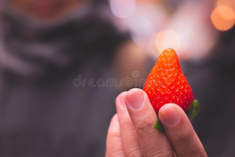 Grande une exposition japonaise de fraise à la main de personnes photos stock