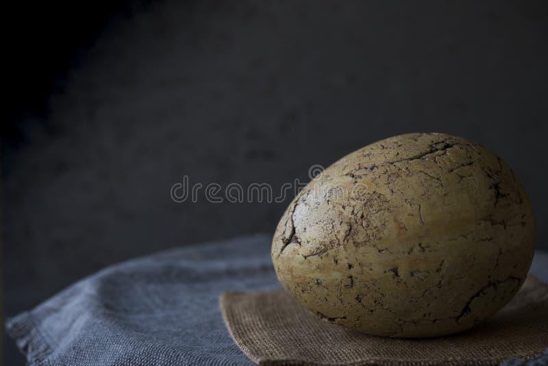 Grande uovo di Pasqua d'annata decorativo sulla tovaglia grigia Fondo nero, spazio per testo immagine stock libera da diritti
