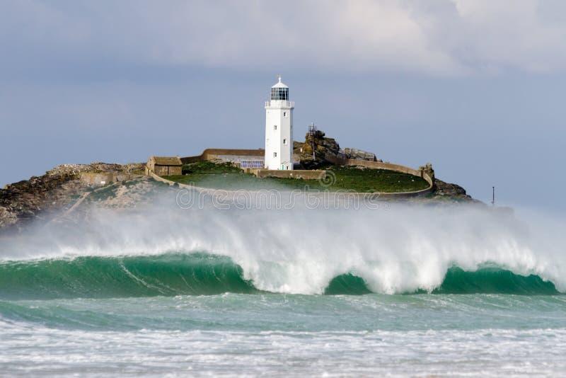 Grande vague de rupture devant le phare photographie stock