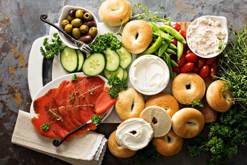 Grande vassoio della prima colazione con i bagel, il salmone affumicato e le verdure fotografie stock