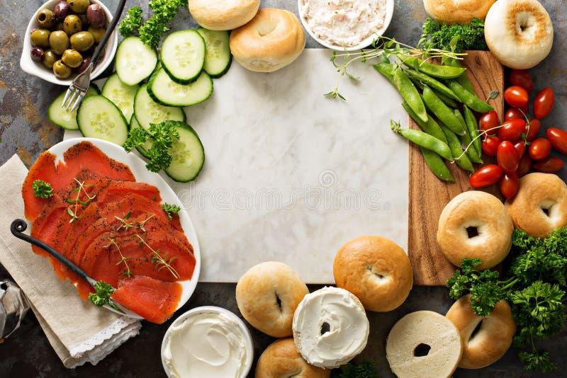 Grande vassoio della prima colazione con i bagel, il salmone affumicato e le verdure fotografia stock libera da diritti
