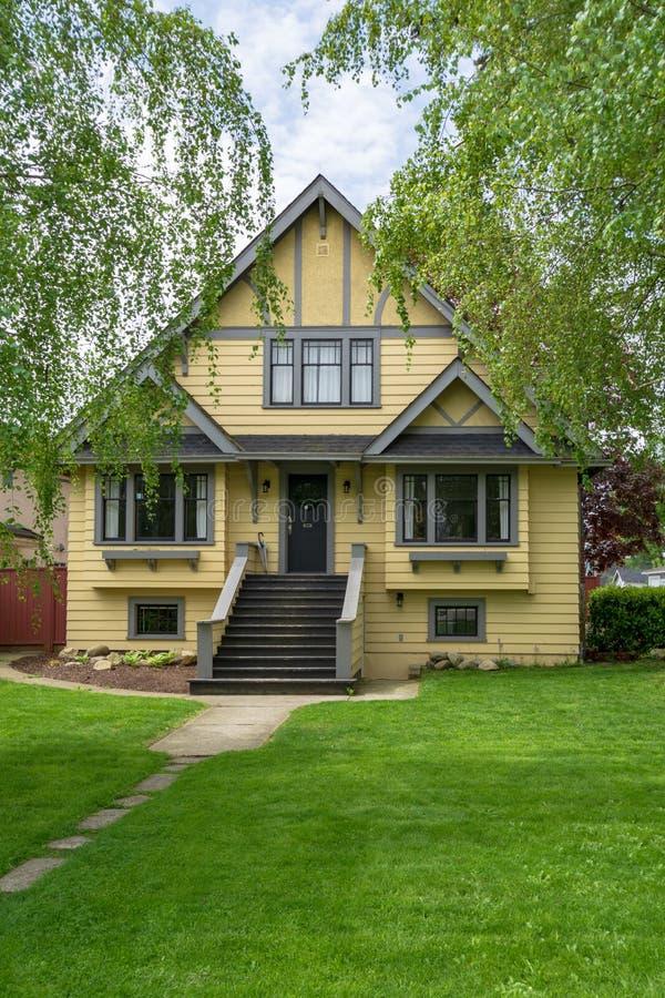 Grande vecchia casa gialla della famiglia con l'iarda anteriore di spacios fotografie stock libere da diritti