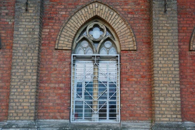 Grande vecchia finestra dietro le barre su un muro di mattoni di una costruzione fotografie stock libere da diritti