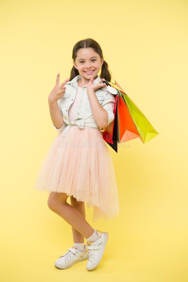Grande vente vendredi noir Paniers heureux de prise de fille sur le fond jaune Sourire d'enfant avec le geste de main de victoire image stock