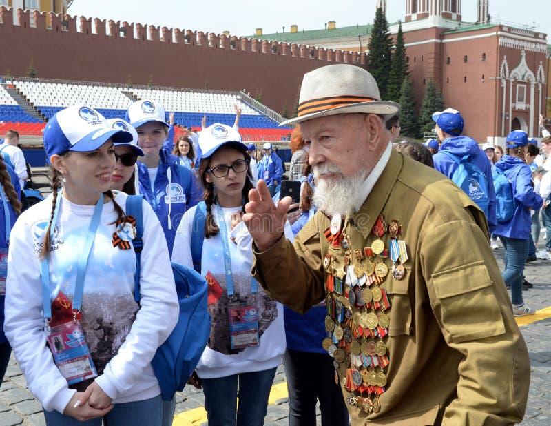 Grande veterano de guerra patriótico Vladimir Burkov no quadrado vermelho de Moscou com os voluntários durante a celebração de Vi foto de stock