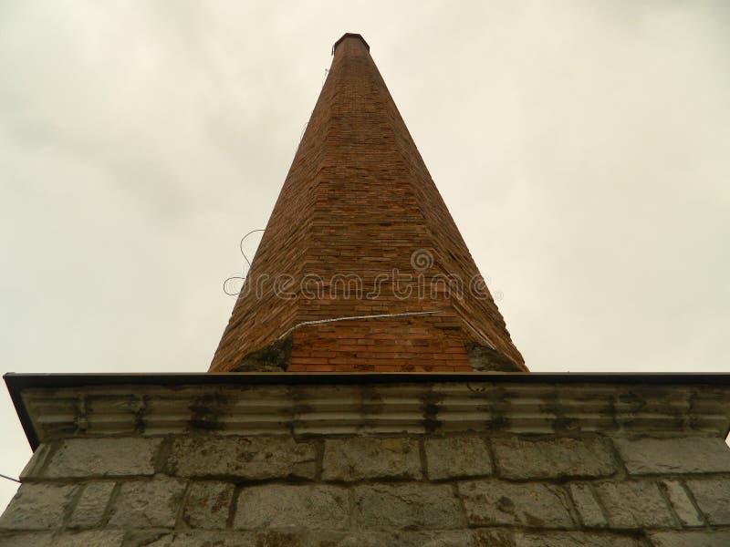 Grande vieille cheminée d'usine fabriquée à partir de la pierre et les briques photographie stock libre de droits