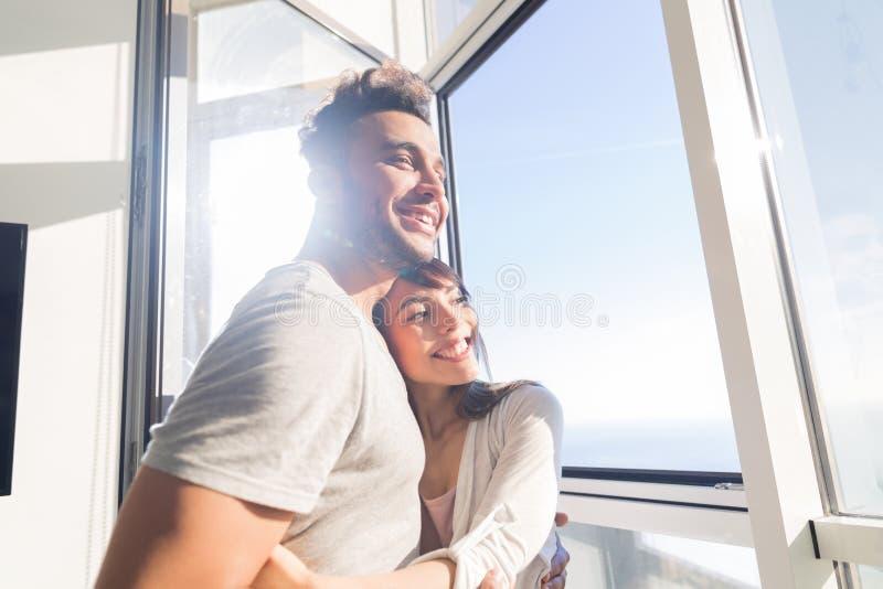 Grande vista panoramica del mare della finestra del giovane delle coppie appartamento moderno di abbraccio, uomo della corsa dell immagini stock