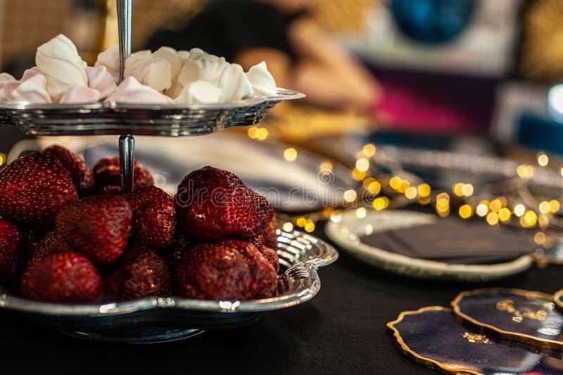 Grandes baies rouges de la fraise et des morceaux blancs de guimauve dans les niveaux argentés du cru 2 servant le plat sur la ta photo stock