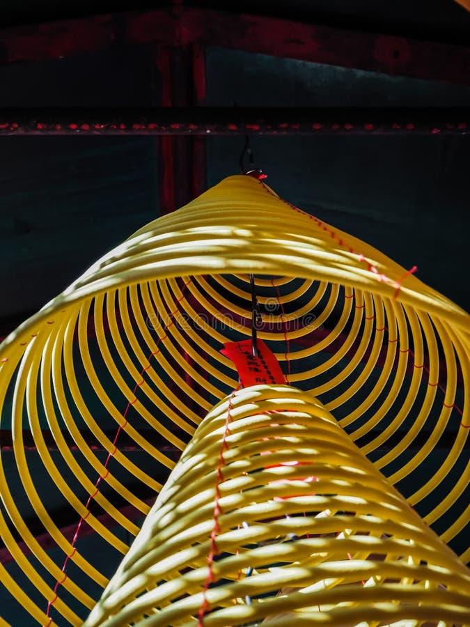 Grandes bobines jaunes multiples d'encens accrochant dans les piles du plafond dans un temple chinois image libre de droits