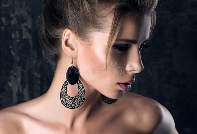 Grandes boucles d'oreille Portrait de plan rapproché dans les ombres d'une jeune femme dans le profil images stock