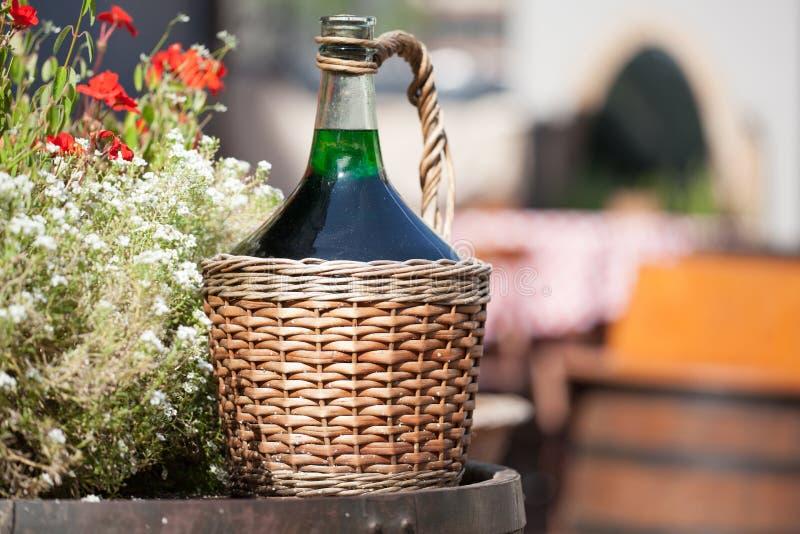 Grandes bouteilles de vin de vintage dans le panier en osier sur un baril image libre de droits
