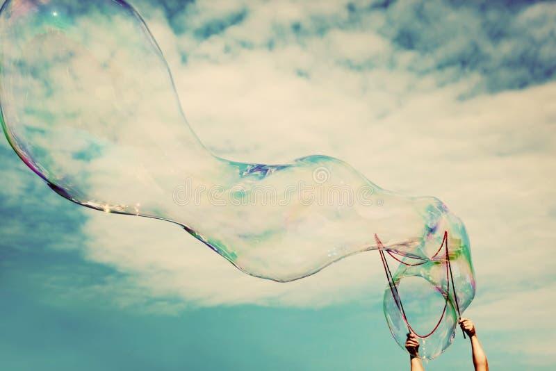 Grandes bulles de savon de soufflement dans le ciel Liberté de vintage, concepts d'été photos stock