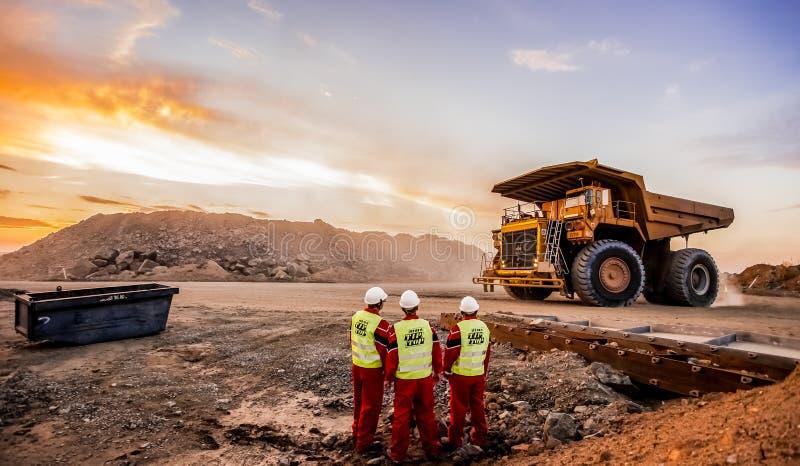 Grandes caminhões basculantes que transportam o minério da platina para processar com os inspetores da segurança de mineração no  fotos de stock