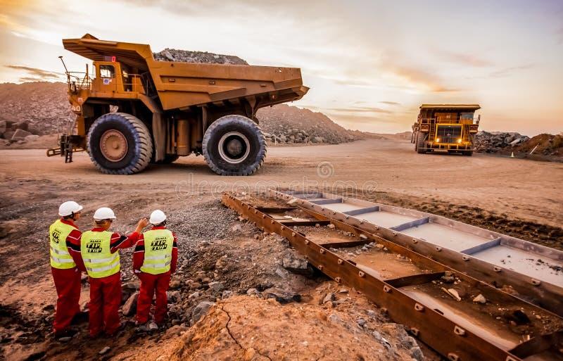 Grandes caminhões basculantes que transportam o minério da platina para processar com os inspetores da segurança de mineração no  fotos de stock royalty free