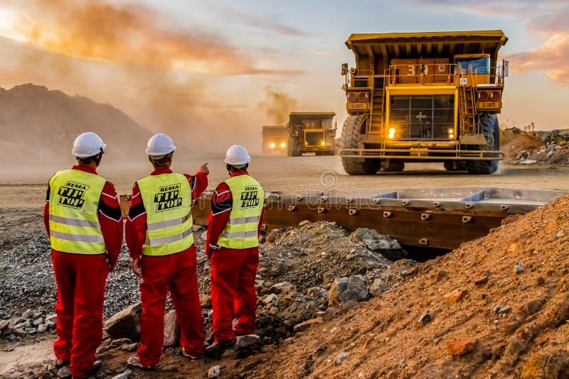 Grandes caminhões basculantes que transportam o minério da platina para processar com os inspetores da segurança de mineração no  imagem de stock royalty free