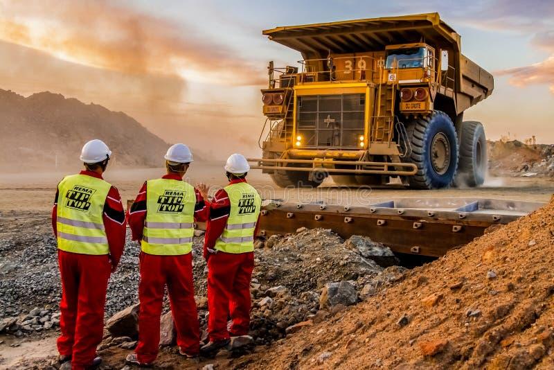 Grandes caminhões basculantes que transportam o minério da platina para processar com os inspetores da segurança de mineração no  imagens de stock