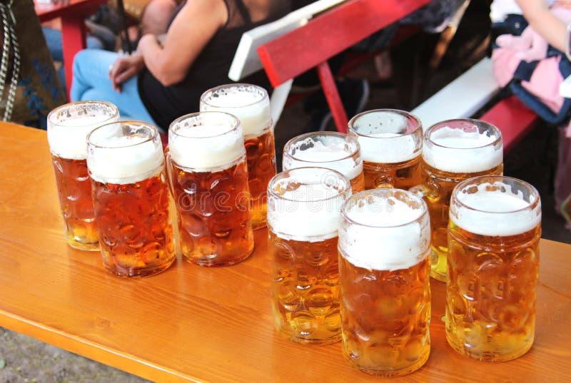 Grandes canecas de cerveja enchidas em uma tabela fotos de stock