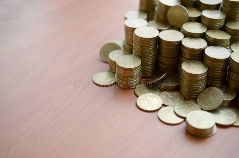 Grandes cantidades de monedas brillantes ucranianas antiguas de 1 jrivnia se acercan a la mesa de madera El concepto de negocios  imagen de archivo libre de regalías