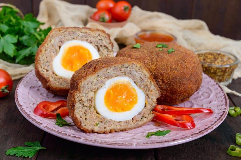 Grandes costoletas suculentas enchidas com ovo cozido em um CCB de madeira escuro imagens de stock