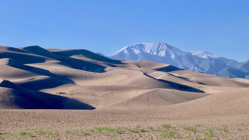 Grandes dunas de arena y montañas nevosas fotografía de archivo libre de regalías