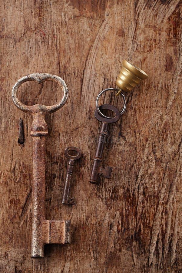 Grandes e chaves oxidadas pequenas do metal do vintage no backgroun de madeira velho fotografia de stock