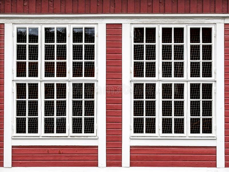 Grandes fenêtres sur un mur en bois rouge images stock