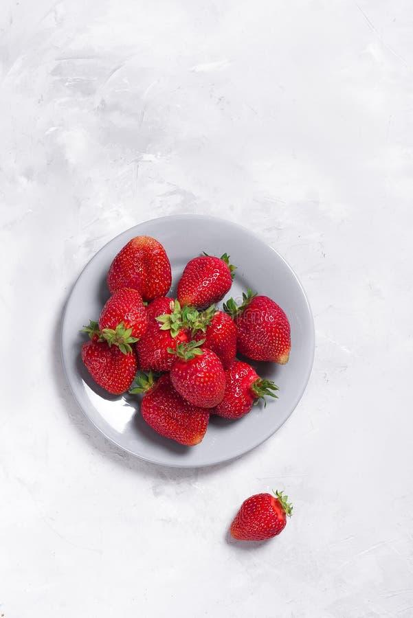 Grandes fraises fraîches sur un fond gris-clair photographie stock