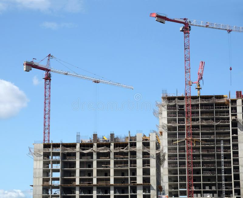 Grandes grues à tour de levage et section supérieure du bâtiment moderne de construction dans une ville au-dessus de ciel bleu av photos stock