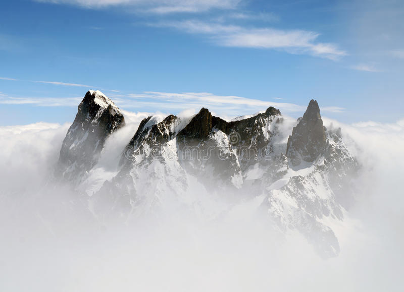 The Grandes Jorasses and Dent du Géant mountains in the fog stock photography