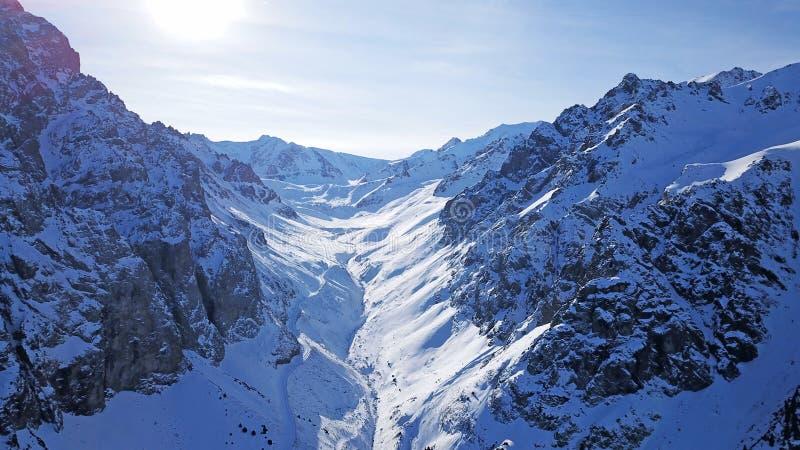 Grandes montanhas e rochas cobertas com a neve Desfiladeiro longo A represa é coberta com a neve imagens de stock