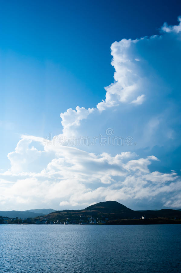 Grandes nuvens billowing acima da vila litoral fotos de stock royalty free