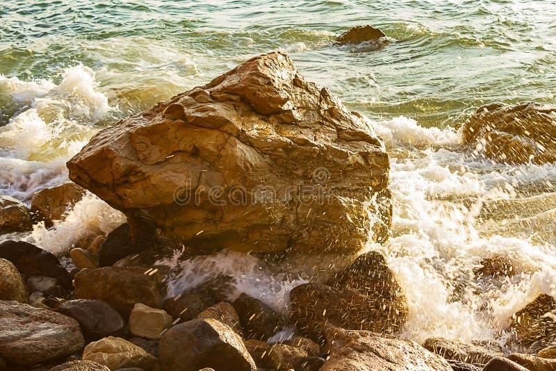 Grandes pedregulhos ásperos com as reflexões de incandescência molhadas de espirrar a onda cercada pelo respingo da espuma e da á imagens de stock royalty free