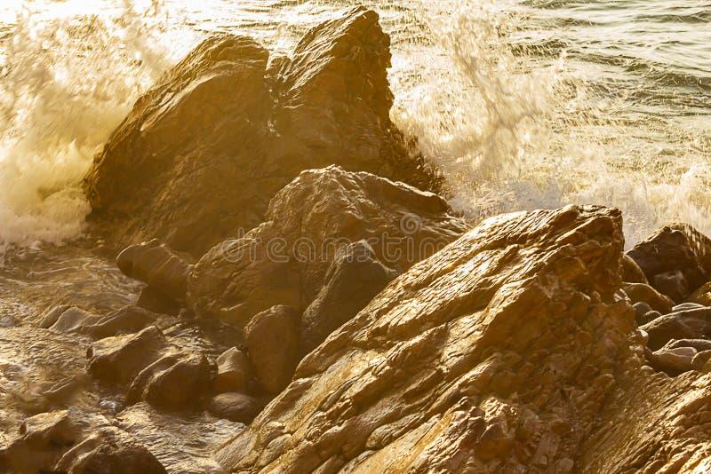 Grandes pedregulhos ásperos com as reflexões de incandescência molhadas de espirrar a onda imagem de stock royalty free