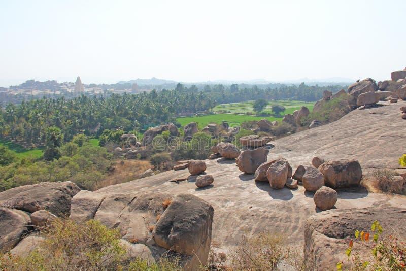 Grandes pierres dans Hampi, Karnataka, Inde Belle vallée verte des gisements et des palmiers de riz image stock
