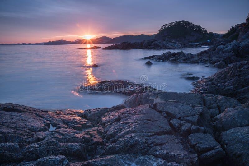 Grandes pierres et la réflexion du soleil dans les vagues de la mer au coucher du soleil/à aube images stock
