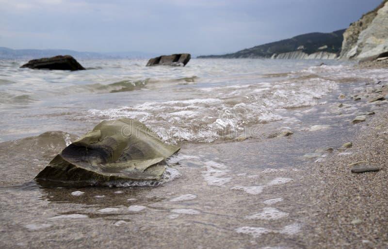 Grandes pierres sur le bord de mer Sable humide, l'eau transparente ciel obscurci nuageux photo stock