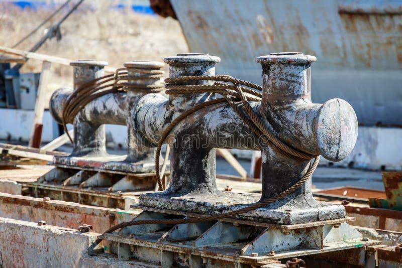 Grandes postes de amarração do metal com cabos entrançados de aço enrolados para amarrar navios imagens de stock